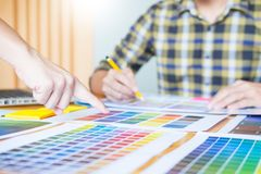 Professional Creative architect graphic desiner occupation choosing the Color pantone palette samples for project on office desk. Top computer royalty free stock images