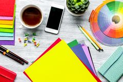 Professional creative graphic designer desk on wooden background. Professional creative graphic designer desk with tools, mobile and cup on light wooden stock images