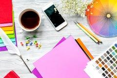 Professional creative graphic designer desk on wooden background top view. Professional creative graphic designer desk with tools, mobile and cup on light wooden stock image