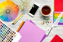 Professional creative graphic designer desk on wooden background top view. Professional creative graphic designer desk with tools, mobile and cup on light wooden stock images
