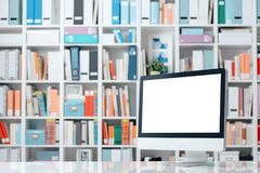 Professional workspace with computer and shelves. Professional creative workspace with computer on a white desktop and colorful folders on the shelves Royalty Free Stock Photo