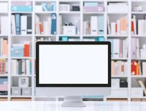 Professional workspace with computer and shelves. Professional creative workspace with computer on a white desktop and colorful folders on the shelves Royalty Free Stock Image