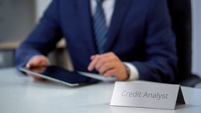 Professional credit analyst using tablet pc, checking company financial history. Stock photo royalty free stock image
