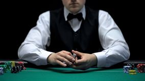 Professional croupier holding cards, ready for poker game in casino, gambling. Stock photo stock photos