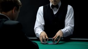 Professional croupier shuffling cards on green table for businessman, poker game. Stock photo royalty free stock photo