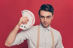 Professional, cunning magician, illusionist, gambler in casual outfit, glasses, holding, showing set deck of card near face, stand. Ing over red background Royalty Free Stock Images
