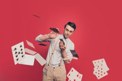 Professional, cunning magician, illusionist, gambler in casual outfit, glasses, throwing, sending cards to the camera, standing ov. Er red background Stock Photography