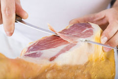 Professional cutting of serrano ham Stock Photos