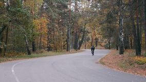 Professional cyclist in black helmet and cycling apparel is intensive training on road bike in fall city park. Male young athlete. Riding on bicycle in autumn stock footage
