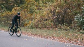 Professional cyclist in black sportswear and helmet riding on road bike in autumn city park. Man intensive training on road bicycl. E in fall park. Cycling stock footage