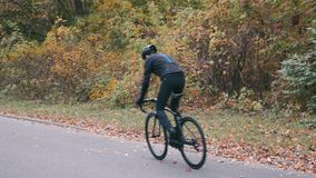 Professional cyclist in black sportswear and helmet riding on road bike in autumn city park. Man intensive training on road bicycl. E in fall park. Cycling stock video