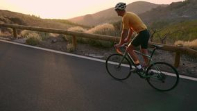 A professional cyclist in a helmet and sports equipment rides on a mountain highway at sunset in slow motion. Steadicam