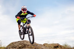 Professional Cyclist Jumping over Rock on the Mountain Bike on the Rocky Hill. Extreme Sport Concept. Space for Text. Stock Photography
