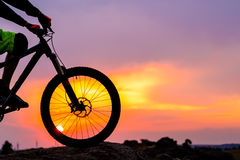 Professional Cyclist Resting with Down Hill Bike on the Rock at Sunset. Stock Photos