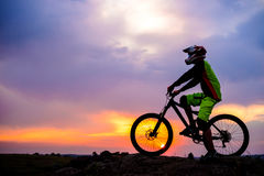 Professional Cyclist Resting with Down Hill Bike on the Rock at Sunset. Extreme Sport. Stock Photos
