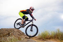 Professional Cyclist Riding the Bike Down Rocky Hill. Extreme Sport Concept. Space for Text. Royalty Free Stock Image