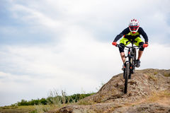 Professional Cyclist Riding the Bike Down Rocky Hill. Extreme Sport Concept. Space for Text. Stock Images