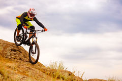 Professional Cyclist Riding the Bike Down Rocky Hill. Extreme Sport Concept. Space for Text. Stock Photos