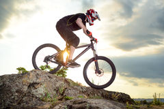 Professional Cyclist Riding the Bike Down Rocky Hill at Sunset. Extreme Sport. Royalty Free Stock Images