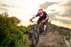 Professional Cyclist Riding the Bike Down Rocky Hill at Sunset. Extreme Sport. Stock Photo
