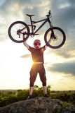 Professional Cyclist Riding the Bike Down Rocky Hill at Sunset. Extreme Sport. Stock Photography