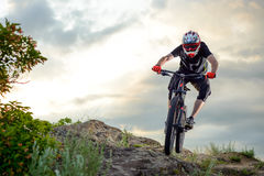 Professional Cyclist Riding the Bike Down Rocky Hill at Sunset. Extreme Sport. Stock Image