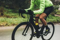 Professional cyclist riding bike. Outdoors. Male athlete in cycling gear practising on wet road. Cropped shot royalty free stock photos