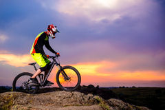 Professional Cyclist Riding the Bike on the Rock at Sunset. Extreme Sport Concept. Space for Text. Royalty Free Stock Photography
