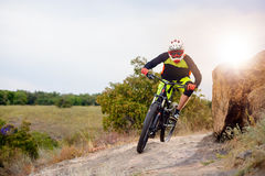 Professional Cyclist Riding the Bike at the Rocky Trail. Extreme Sport Concept. Space for Text. Royalty Free Stock Image