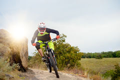Professional Cyclist Riding the Bike at the Rocky Trail. Extreme Sport Concept. Space for Text. Stock Photos