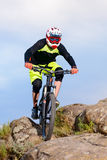 Professional Cyclist Riding the Bike on Top of the Rock. Extreme Sport Concept. Royalty Free Stock Images
