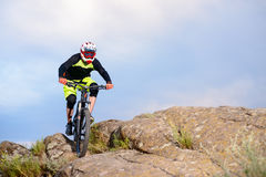Professional Cyclist Riding the Bike on the Top of the Rock. Extreme Sport Concept. Space for Text. Royalty Free Stock Photography