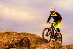 Professional Cyclist Riding the Bike on the Top of the Rock. Extreme Sport Concept. Space for Text. Stock Photos
