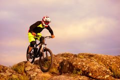Professional Cyclist Riding the Bike on the Top of the Rock. Extreme Sport Concept. Space for Text. Stock Photo