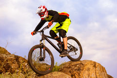 Professional Cyclist Riding the Bike on the Top of the Rock. Extreme Sport Concept. Space for Text. Stock Photography