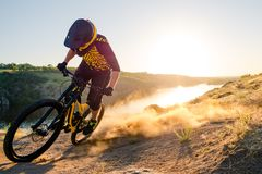Cyclist Riding the Mountain Bike on the Summer Rocky Trail at the Evening. Extreme Sport and Enduro Cycling Concept. Professional Cyclist Riding the Downhill stock images