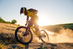 Cyclist Riding the Mountain Bike on the Summer Rocky Trail at the Evening. Extreme Sport and Enduro Cycling Concept. Royalty Free Stock Photography
