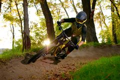 Professional Cyclist Riding the Mountain Bike on the Autumn Forest Trail. Extreme Sport and Enduro Cycling Concept. royalty free stock image