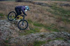 Professional Cyclist Riding Mountain Bike Down the Rocky Hill. Extreme Sport and Enduro Biking Concept. Stock Image