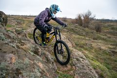 Professional Cyclist Riding Mountain Bike Down the Rocky Hill. Extreme Sport and Enduro Biking Concept. Royalty Free Stock Images