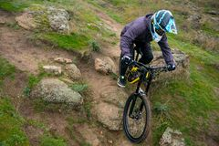 Professional Cyclist Riding Mountain Bike Down the Rocky Hill. Extreme Sport and Enduro Biking Concept. Royalty Free Stock Photo