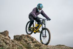 Professional Cyclist Riding Mountain Bike Down the Rocky Hill. Extreme Sport and Enduro Biking Concept. Stock Photo