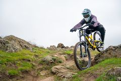 Professional Cyclist Riding Mountain Bike Down the Rocky Hill. Extreme Sport and Enduro Biking Concept. Stock Photography