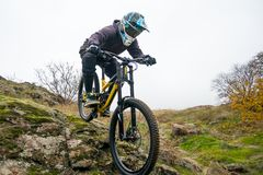 Professional Cyclist Riding Mountain Bike Down the Rocky Hill. Extreme Sport and Enduro Biking Concept. Stock Photos
