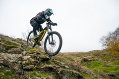 Professional Cyclist Riding Mountain Bike Down the Rocky Hill. Extreme Sport and Enduro Biking Concept. Stock Images
