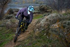 Professional Cyclist Riding Mountain Bike Down the Rocky Hill. Extreme Sport and Enduro Biking Concept. Royalty Free Stock Image