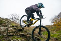 Professional Cyclist Riding Mountain Bike Down the Rocky Hill. Extreme Sport and Enduro Biking Concept. Royalty Free Stock Photos