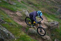 Professional Cyclist Riding Mountain Bike Down the Rocky Hill. Extreme Sport and Enduro Biking Concept. Royalty Free Stock Photography