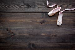 Professional dance shoes. Ballet concept. Pointes on dark wooden background top view copy space. Professional dance shoes. Ballet concept. Pointes on dark wooden Royalty Free Stock Photography