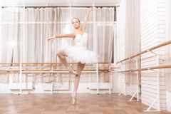 Professional dancer rehearses in ballet class. She trains dance moves. She is dressed in a ballet tutu. She is the professional theater actor Stock Photo